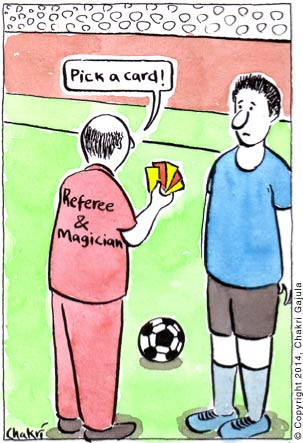 At a football game, the referee with a jersey 'Referee & Magician' pulling out a bunch of yellow and red cards and asking a player to 'Pick a card!'